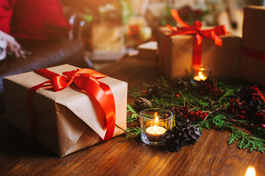 Gift box and candle on wooden table.